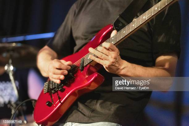 midsection of man playing guitar - ベースギター ストックフォトと画像