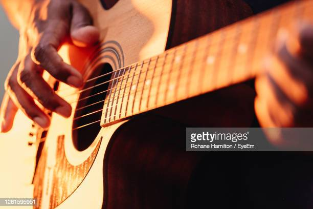 midsection of man playing guitar - hamiltonmusical stockfoto's en -beelden