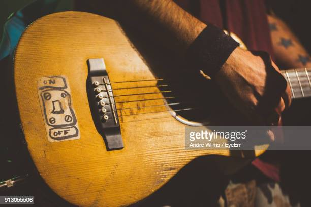 midsection of man playing guitar - andre wilms eyeem stock-fotos und bilder