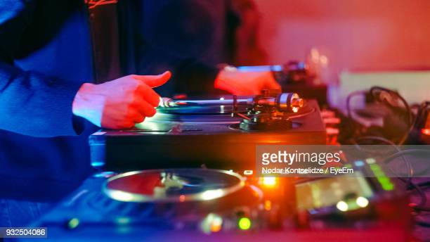 midsection of man playing music at nightclub - club dj stock pictures, royalty-free photos & images
