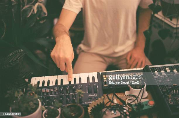 midsection of man playing musical instrument - electronic music stock pictures, royalty-free photos & images