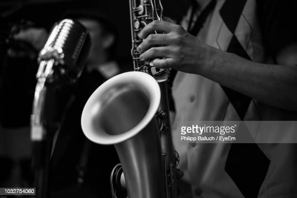 midsection of man playing saxophone during concert - jazz stock pictures, royalty-free photos & images