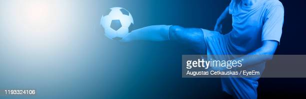 midsection of man playing soccer against black background - cetkauskas stock pictures, royalty-free photos & images