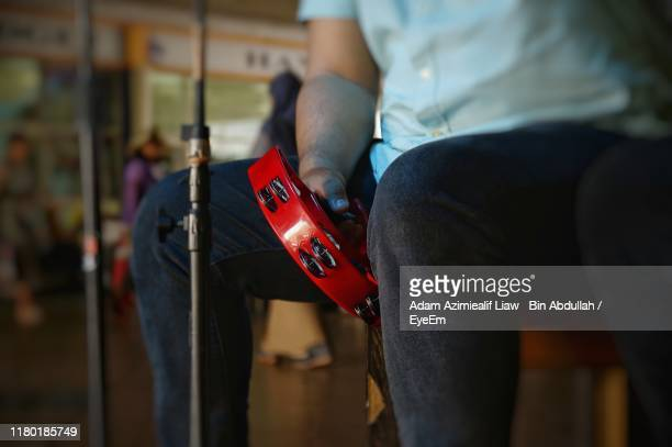 midsection of man playing tambourine - tambourine stock pictures, royalty-free photos & images