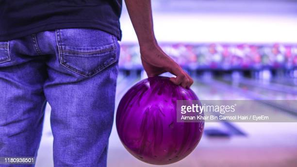 midsection of man playing ten pin bowling - bowling stock pictures, royalty-free photos & images