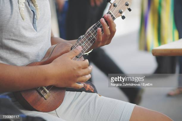 midsection of man playing ukulele - tahiti stock pictures, royalty-free photos & images