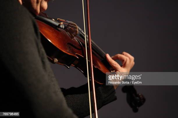 Midsection Of Man Playing Violin Against Gray Background