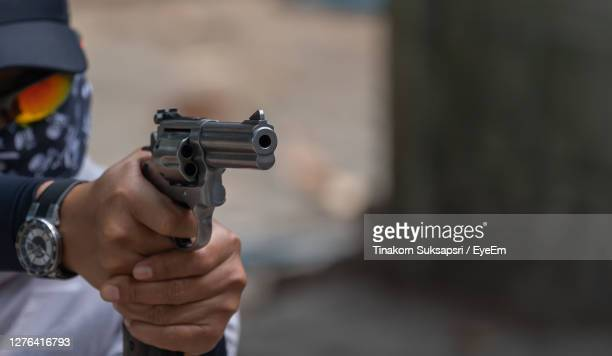 midsection of man pointing gun outdoors - gunman stock pictures, royalty-free photos & images