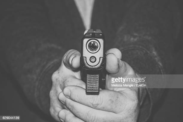 midsection of man pointing gun - gun barrel stock pictures, royalty-free photos & images