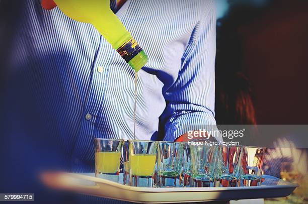 Midsection Of Man Pouring Alcohol In Shot Glass At Bar