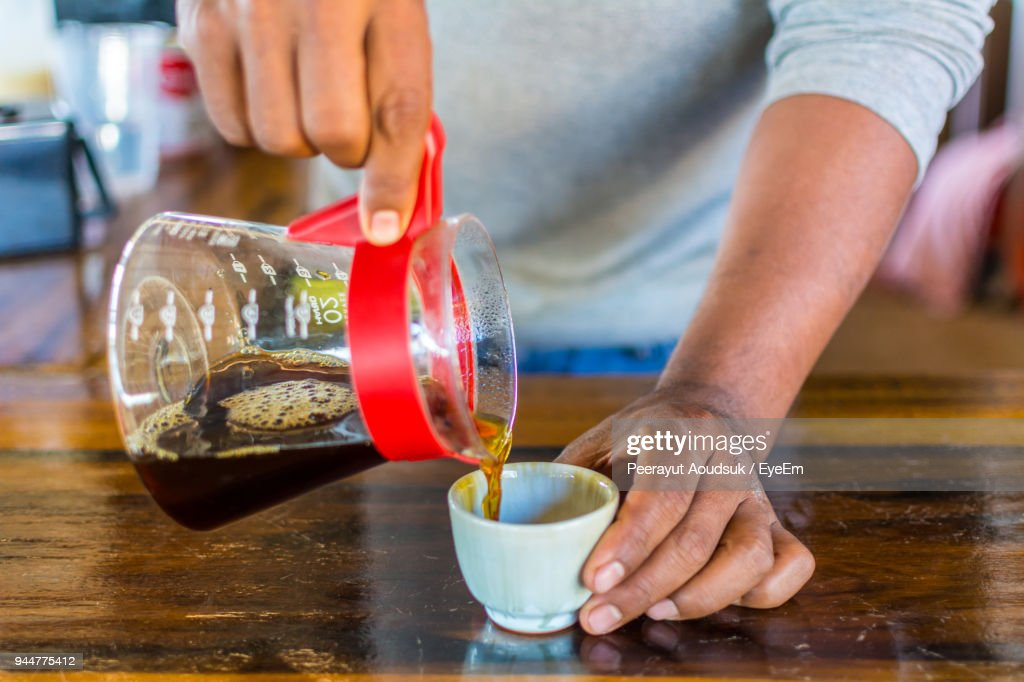 Midsection Of Man Pouring Black Coffee In Cup On Table : Stock Photo