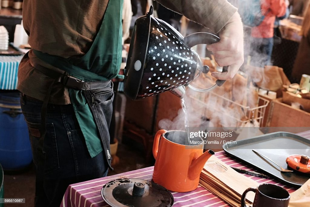 Midsection Of Man Pouring Boiling Water From Kettle At Borough Market : Stock Photo