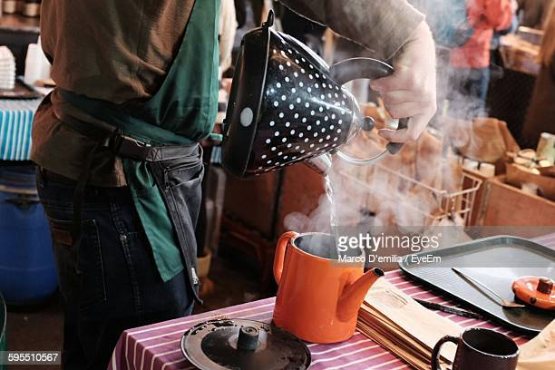 midsection of man pouring boiling water from kettle at borough market - borough market stock pictures, royalty-free photos & images