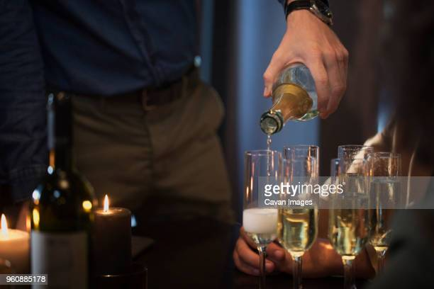 Midsection of man pouring champagne in glasses
