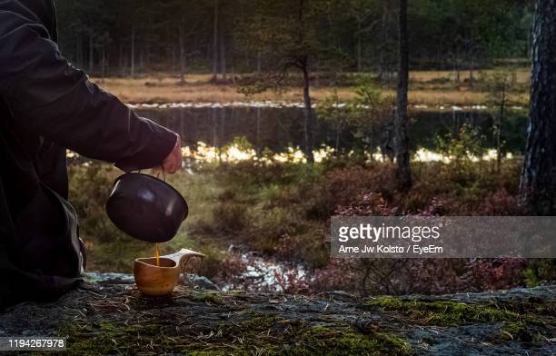 midsection of man pouring drink in container on land in forest - arne jw kolstø stock pictures, royalty-free photos & images