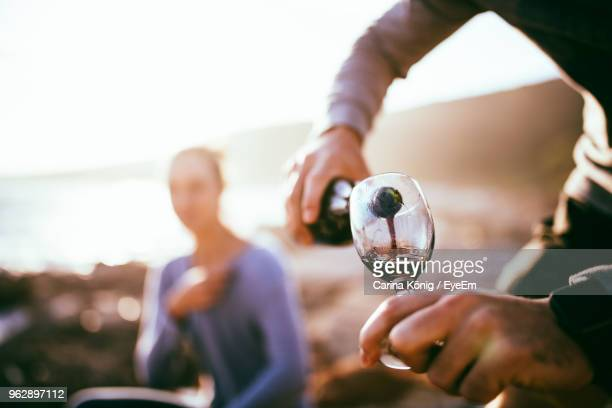 midsection of man pouring red wine while woman sitting in background during sunset - serving size stock photos and pictures