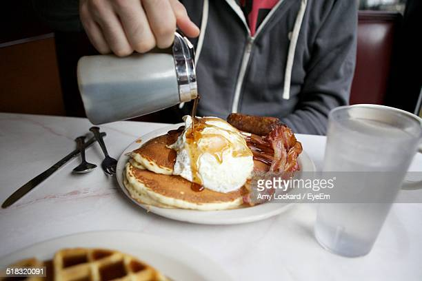 Midsection Of Man Pouring Syrup On Pancake While Sitting On Table