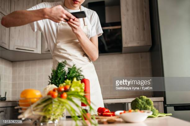 midsection of man preparing food at home - 根菜 ストックフォトと画像