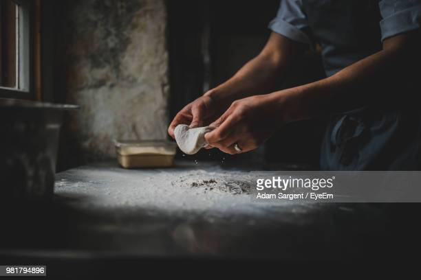 midsection of man preparing food in kitchen - dough stock pictures, royalty-free photos & images