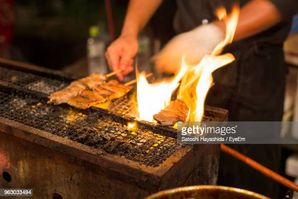 midsection of man preparing food on barbecue grill - ureshino saga stock pictures, royalty-free photos & images
