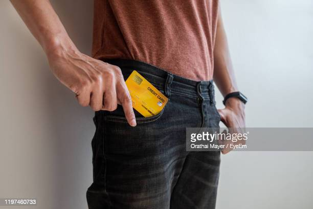 midsection of man putting credit card in pocket against white background - hands in her pants stock pictures, royalty-free photos & images