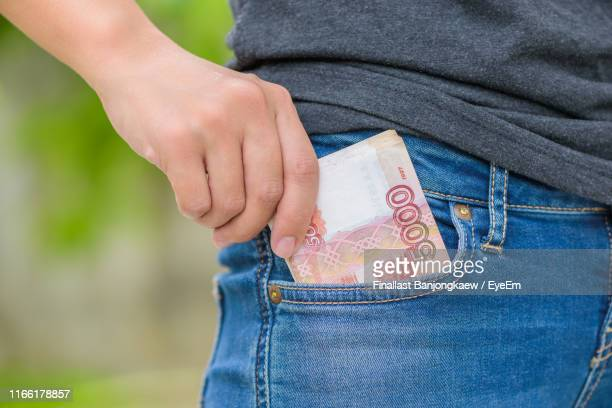 midsection of man putting money in pocket - hands in her pants stock pictures, royalty-free photos & images