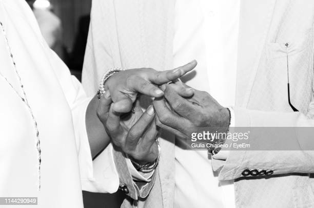 midsection of man putting ring on finger of bride during wedding ceremony - marriage stock pictures, royalty-free photos & images