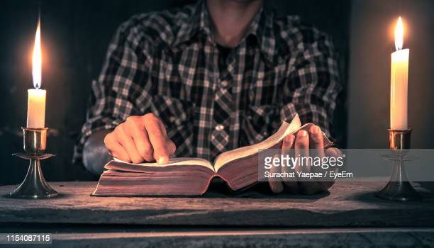 midsection of man reading bible by illuminated candles on table - candlestick holder stock pictures, royalty-free photos & images