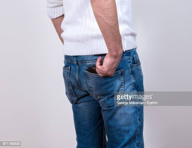 midsection of man removing wallet from his back pocket against white background - hands in her pants - fotografias e filmes do acervo