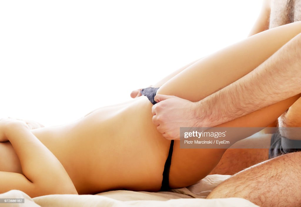 Midsection Of Man Removing Woman Panties Against White Background : Stock Photo