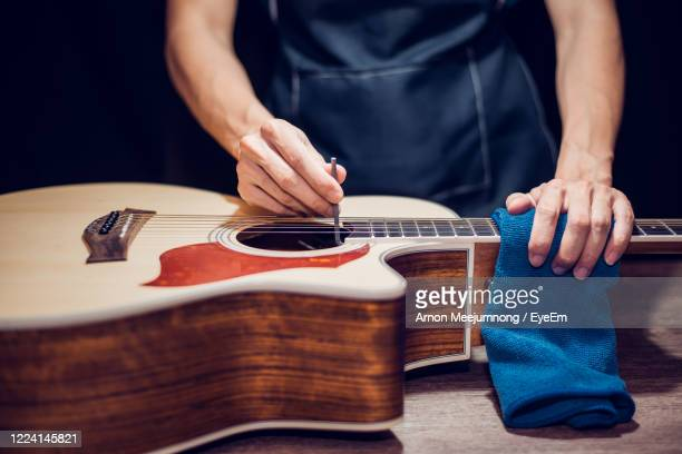 midsection of man repairing guitar - grimes musician stock pictures, royalty-free photos & images