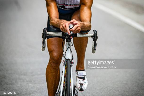 midsection of man riding bicycle - wielrennen stockfoto's en -beelden
