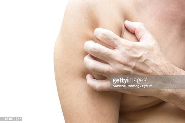 midsection of man scratching against white background - scratching stock pictures, royalty-free photos & images