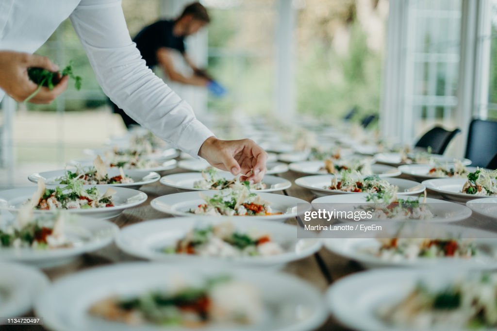 Midsection Of Man Serving Food In Plates On Table At Wedding Ceremony : Stock Photo