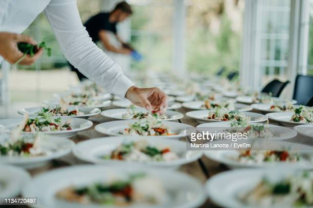 midsection of man serving food in plates on table at wedding ceremony - wedding reception stock photos and pictures