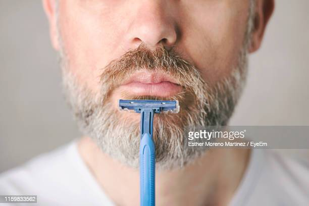 midsection of man shaving against white background - beard stock pictures, royalty-free photos & images