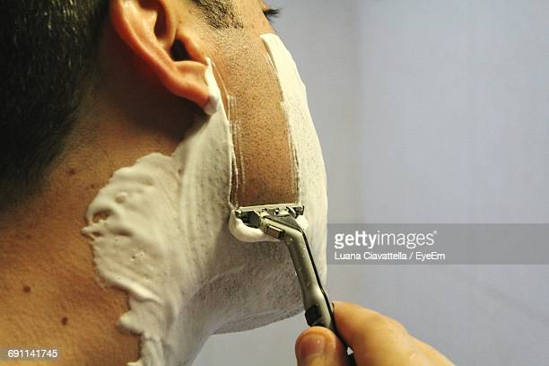 Midsection Of Man Shaving In Bathroom