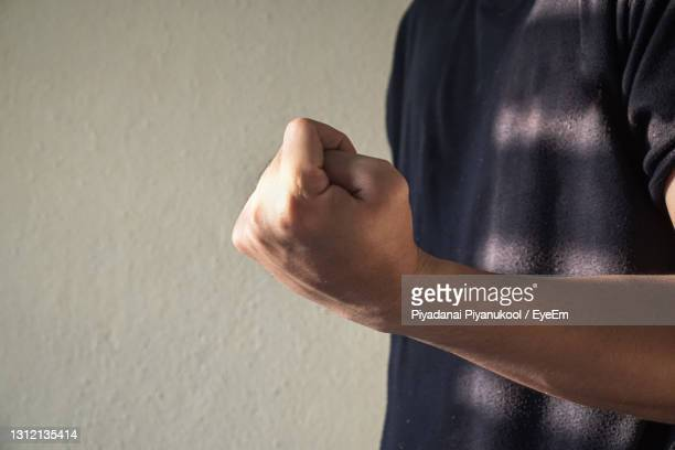 midsection of man showing fist against wall - fist stock pictures, royalty-free photos & images