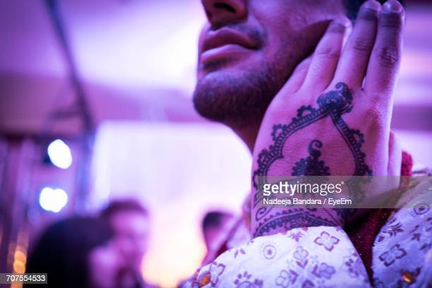 Midsection Of Man Showing Henna Tattoo On Hand At Wedding