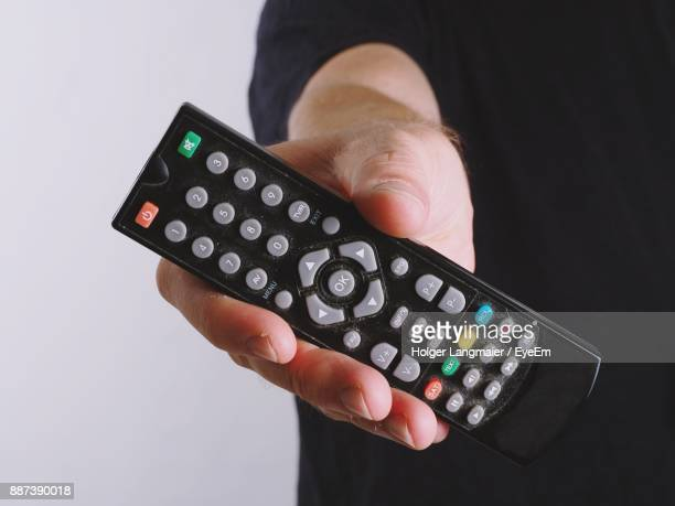 Midsection Of Man Showing Remote Control Against White Background