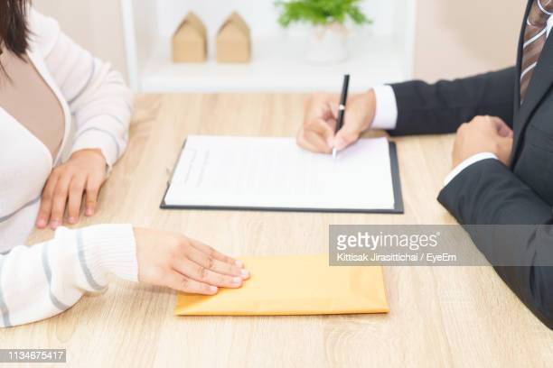 midsection of man signing agreement while woman giving bribe on table at office - corruption stock pictures, royalty-free photos & images