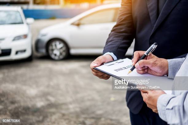Midsection Of Man Signing Car Insurance Form