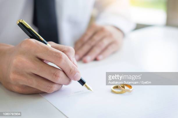 midsection of man signing on divorce paper - 離婚 ストックフォトと画像