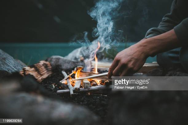 midsection of man sitting by campfire - キャンプファイヤー ストックフォトと画像