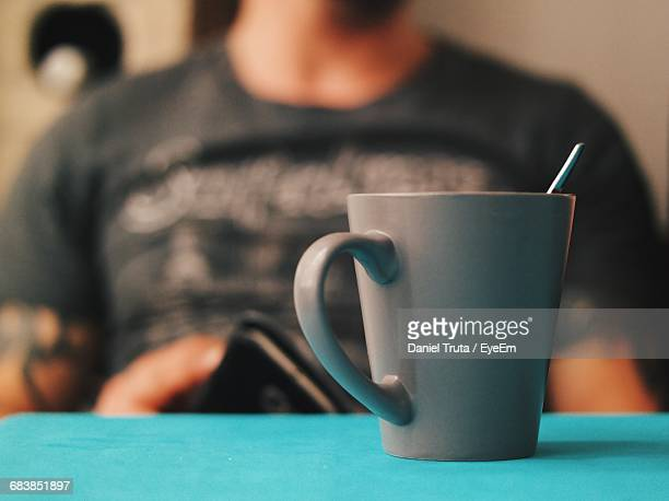 Midsection Of Man Sitting By Coffee On Table