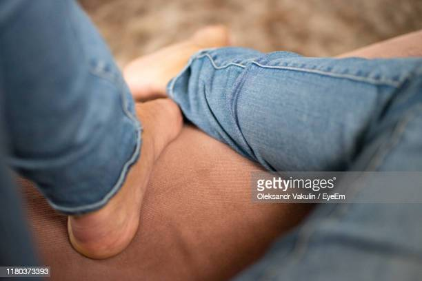 midsection of man sitting on sofa - oleksandr vakulin stock pictures, royalty-free photos & images