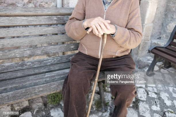 Midsection Of Man Sitting On Wooden Bench
