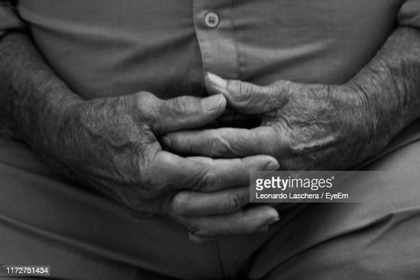 midsection of man sitting with hands clasped - mani incrociate foto e immagini stock