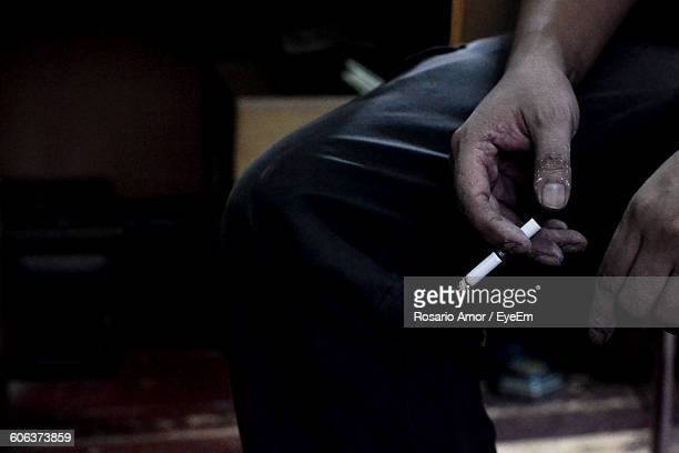Midsection Of Man Smoking At Home