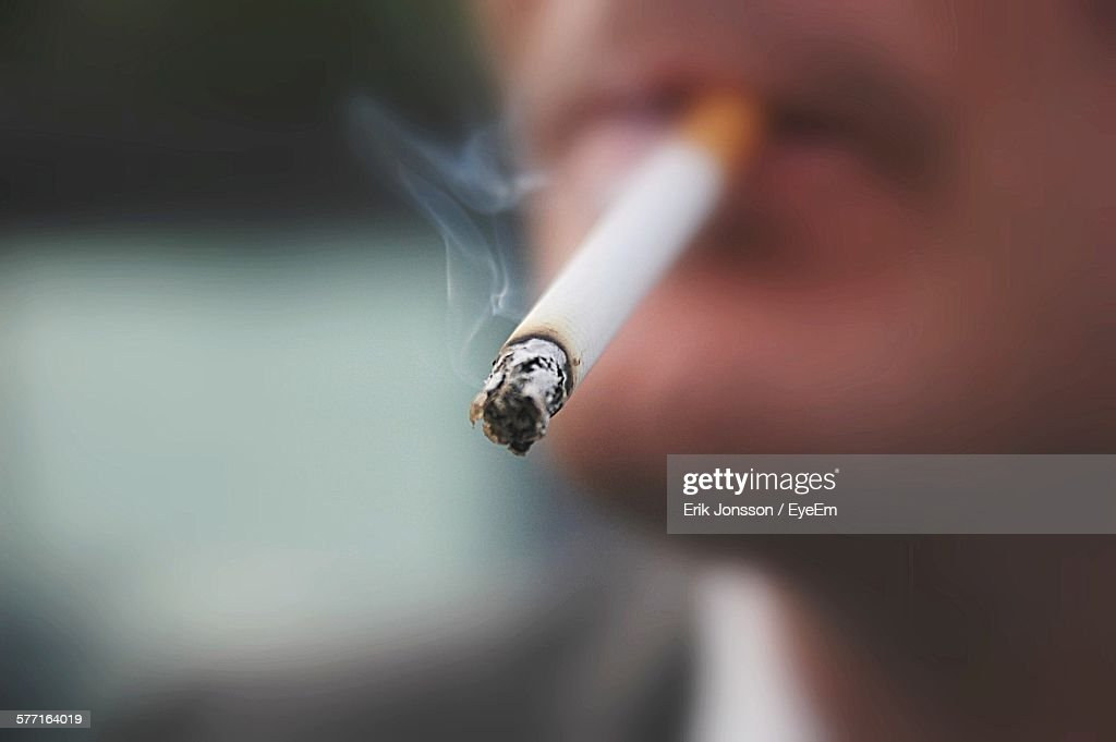 Midsection Of Man Smoking Cigarette : Stock Photo